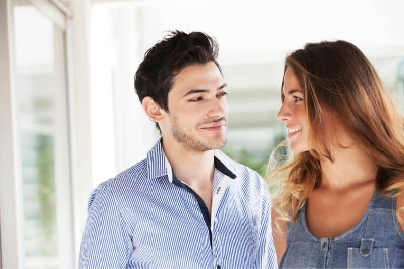 young man and woman flirting outside of the house