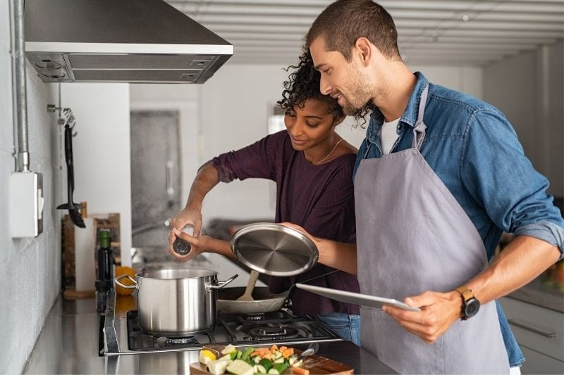 young man helping an african woman cooking inside the kitchen