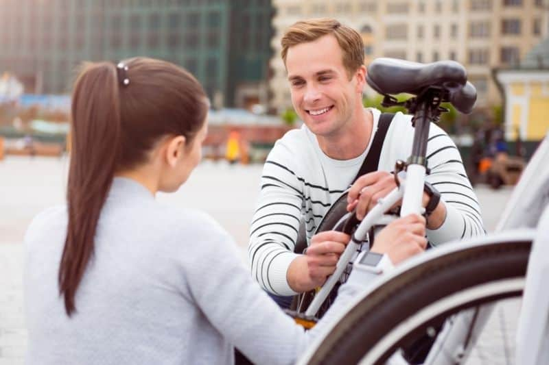 young man looking at a woman while fixing a bike