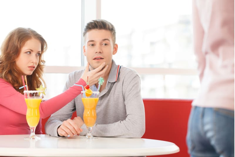 young man looking at lady passing by while being stopped by the woman sitting beside him by the table