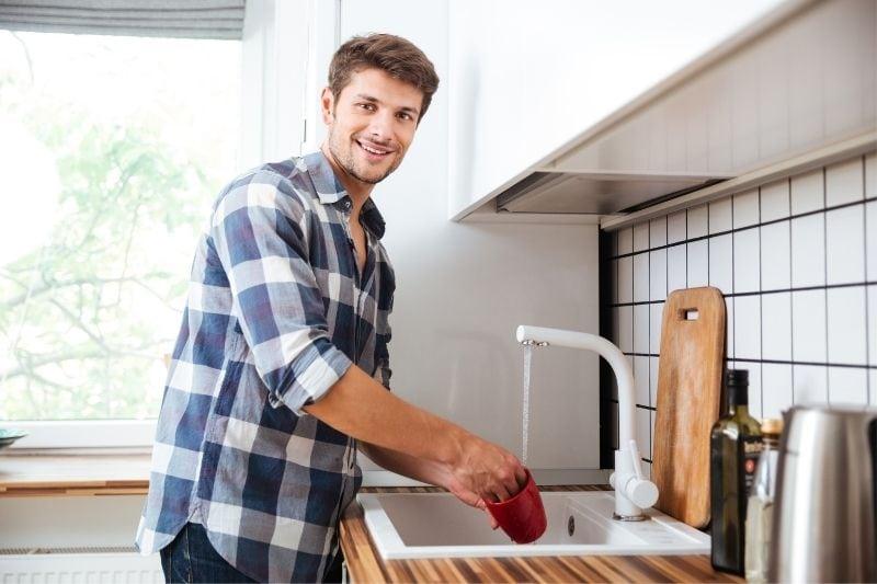 young man washing dish smiling at the camera