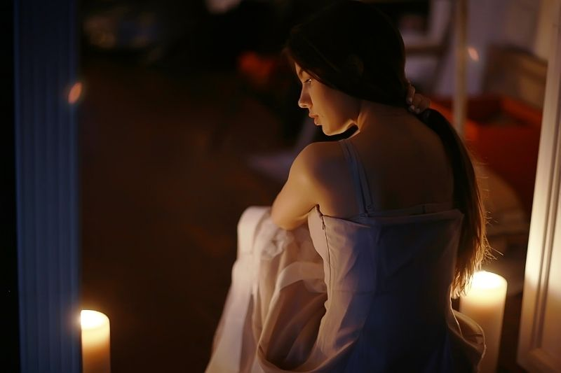 young woman and candles in a romantic set up sitting in a rear view