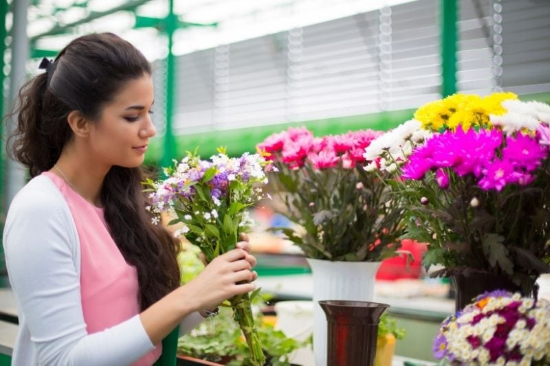 young woman buying flowers at the market holding the bouquet of flowers in sideview image