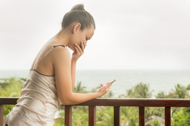 young woman crying looking at the cellphone in the veranda