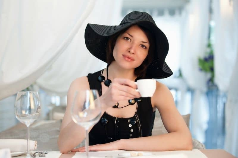 young woman in the restaurant sipping a cup of tea wearing black dress and hat