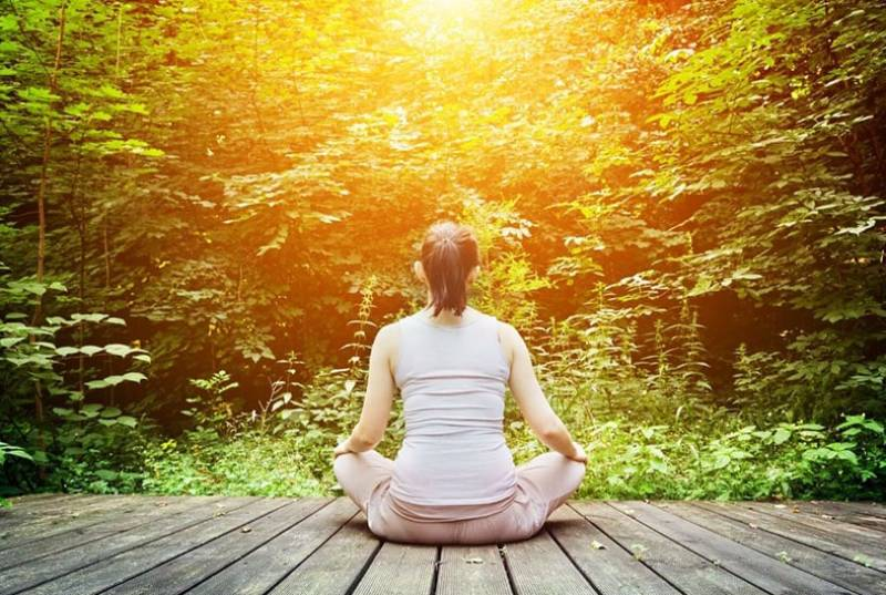 young woman meditates sitting on a wooden platform facing nature