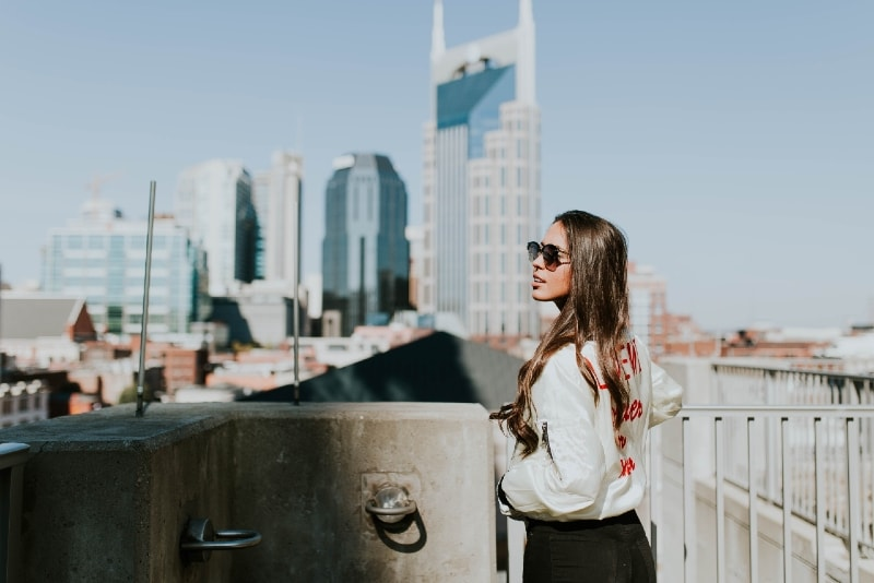 woman with sunglasses standing near hand rails