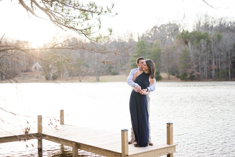 man kissing woman while standing on dock near water