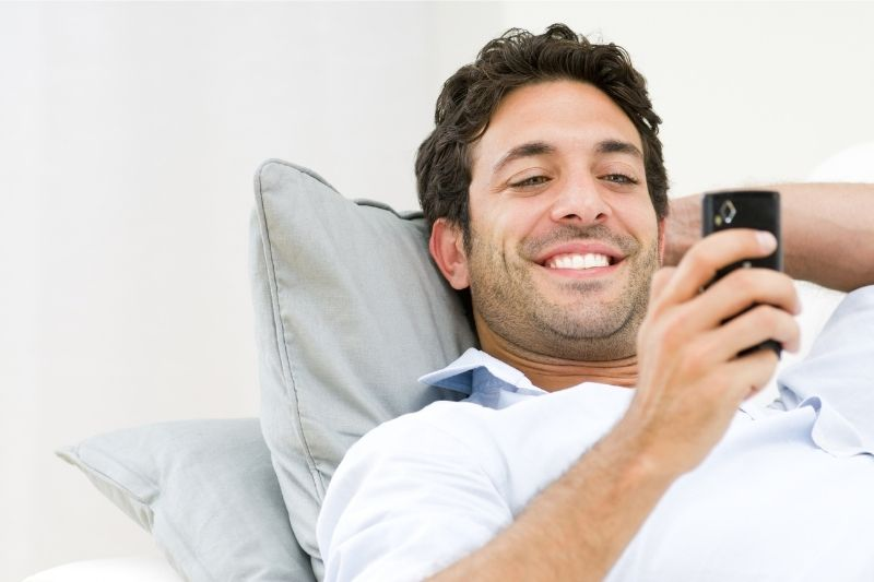 handsome man lying down while texting on his smartphone