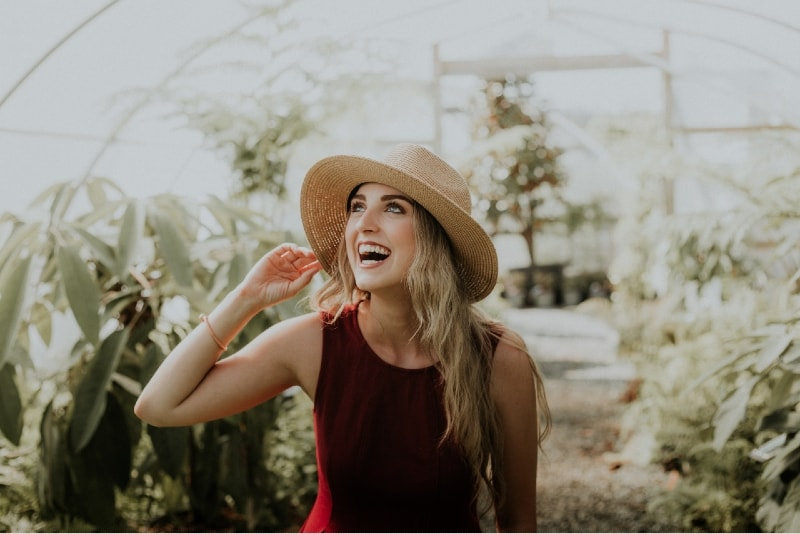 happy woman with hat standing near plants