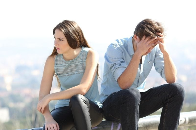 upset man and woman sitting outdoors with blue top and black jeans