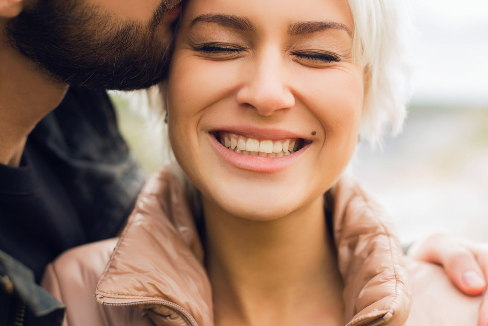 a bearded man kisses a smiling woman on the cheek
