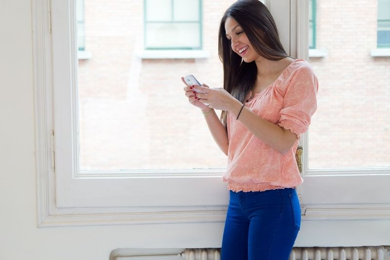 a brunette young woman texting standing near the windows of the house