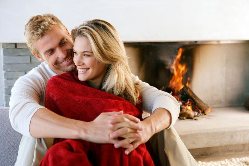adult couple cuddling inside home near the fireplace