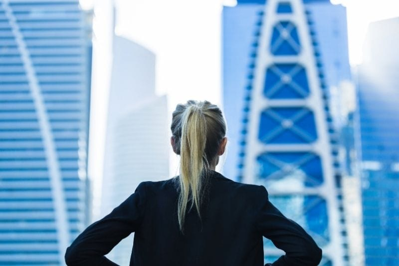 ambitious career woman looking at the high rising building with hands placed on her waist in a rear view