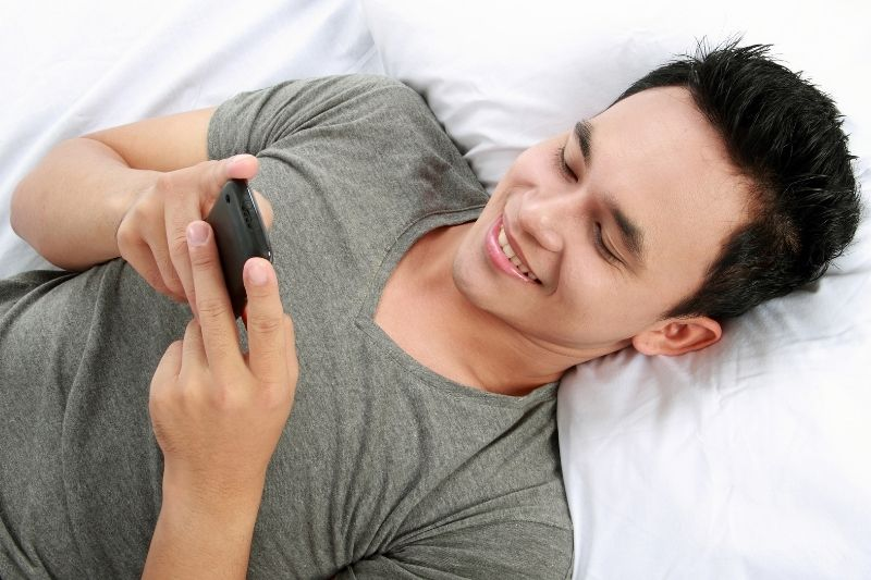 asian man reading message from his cellphone while laying down