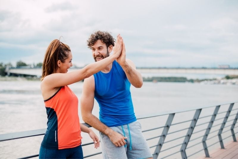 athletic couple giving high five to each other near a body of water