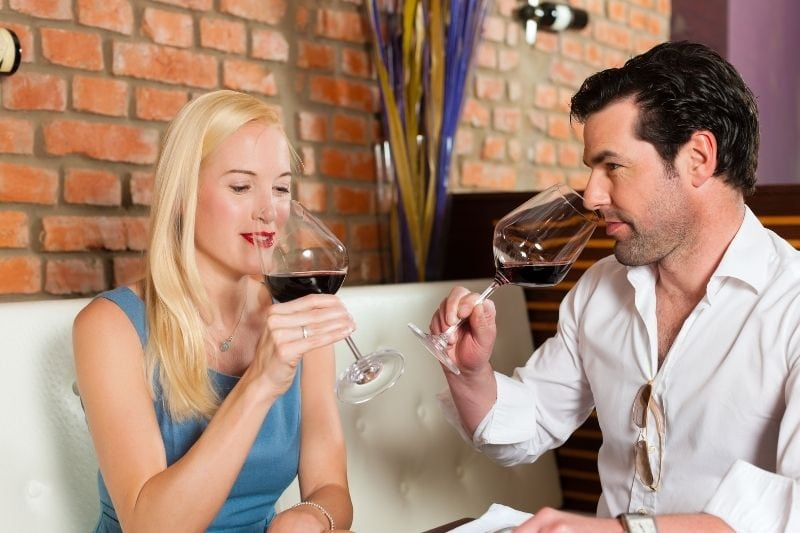 attractive couple drinking wine during their date inside a restaurant