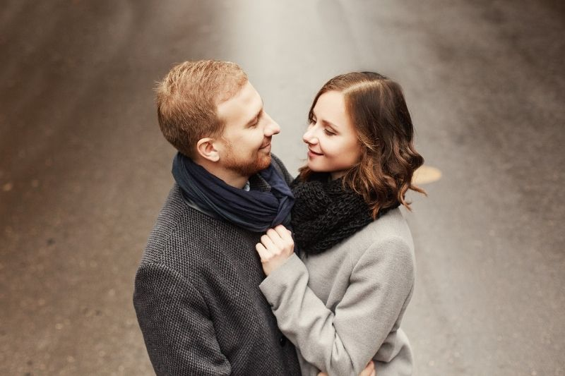 attractive couple standing in the street looking at each other