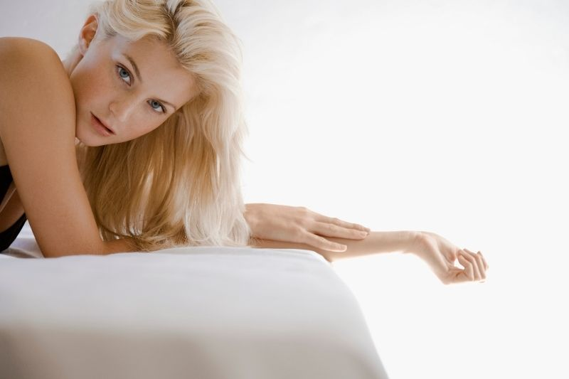 attractive seductive woman with blonde hair lying in bed