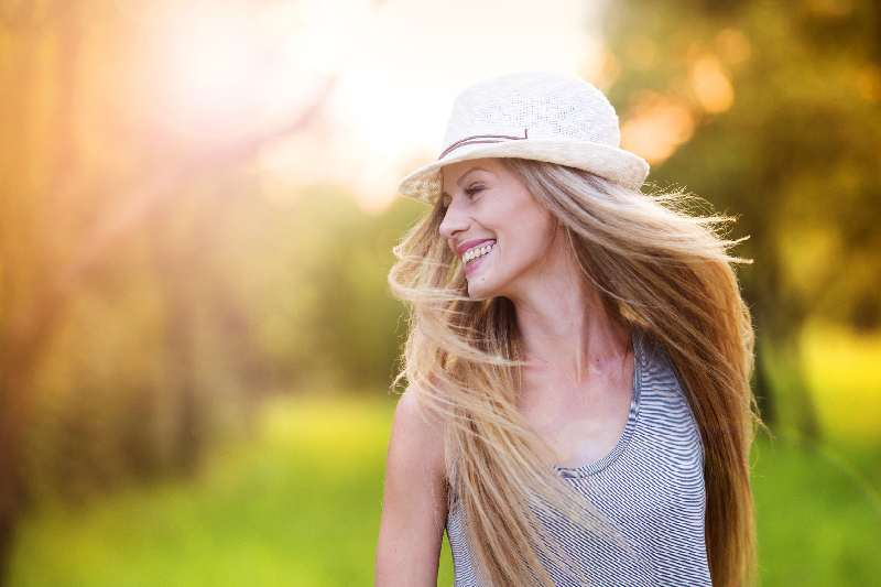 attractive young woman enjoying life under the sun with hat