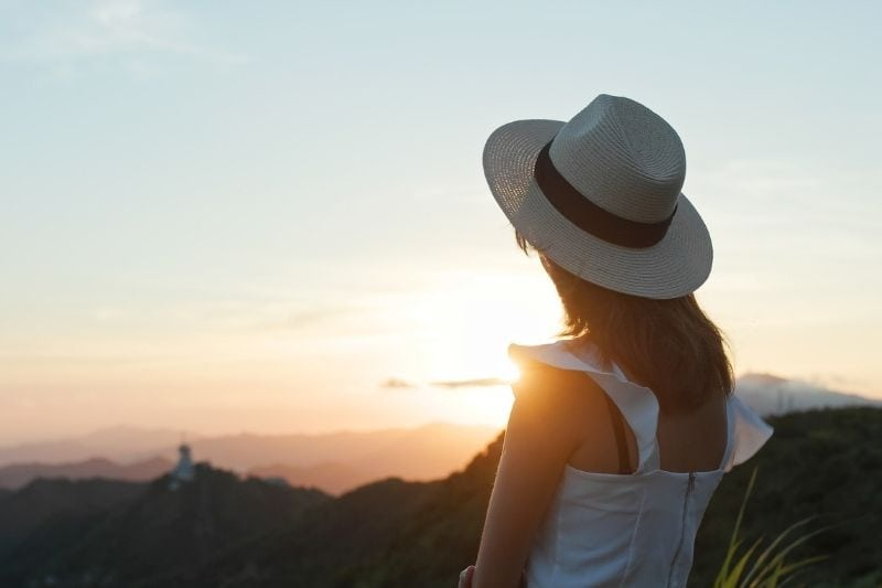 backview of a woman looking at the sunset wearing hat and white dress standing on top of a mountain