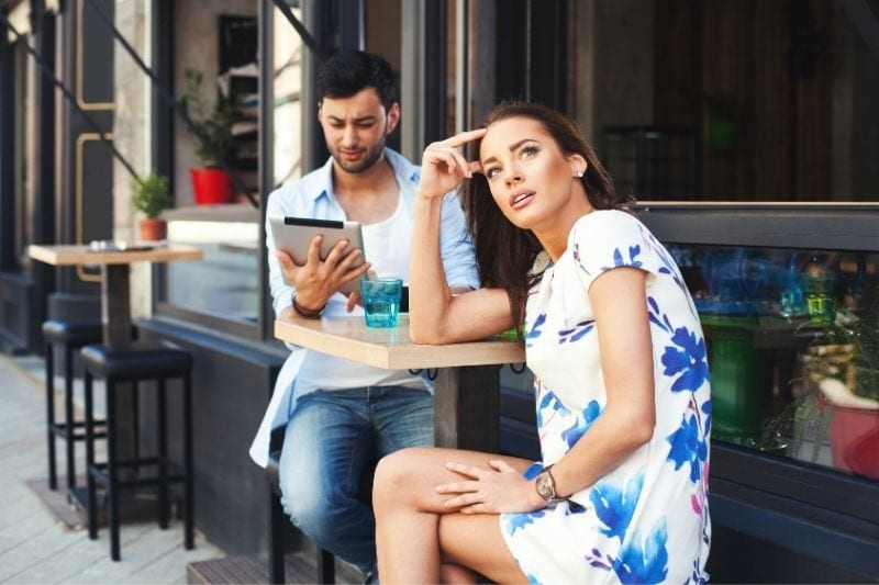 bad date of a woman with a man looking at the tablet in an outdoor chairs of the cafe