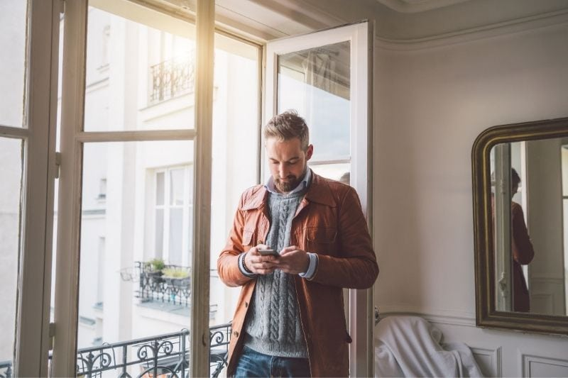 bearded man reading text from his smartphone standing near the glass door inside home