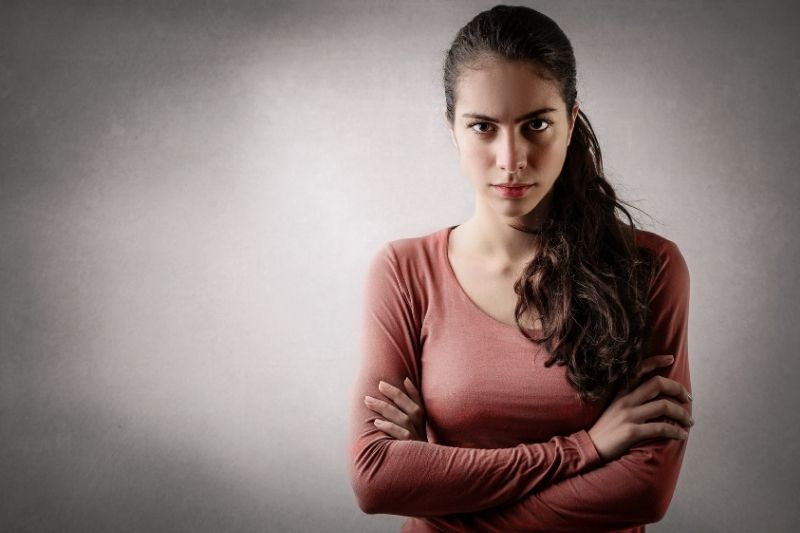 beautiful angry woman with arms crossed standing against a light focused wall