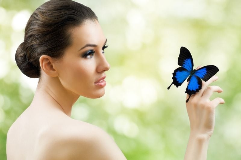 beautiful butterfly woman in sideview with a blue butterfly on her finger