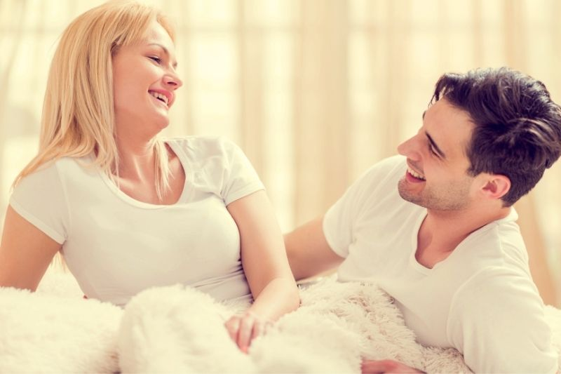 beautiful couple talking cheerfully while in the bed
