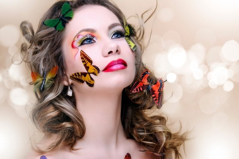 beautiful fashion woman with professional make up surrounded with butterflies of different colors