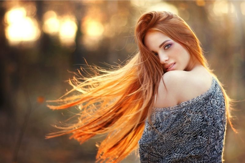 beautiful lady looking back flipping her hair wearing off shoulder top