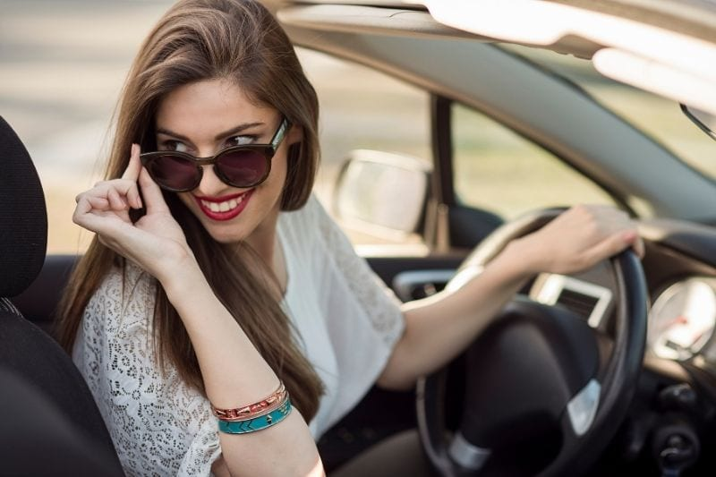 beautiful smiling woman riding a top down car looking at the back holding her sunglasses