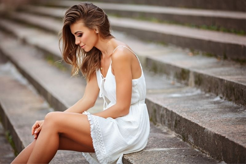beautiful woman sitting in the cement stairs wearing white dress