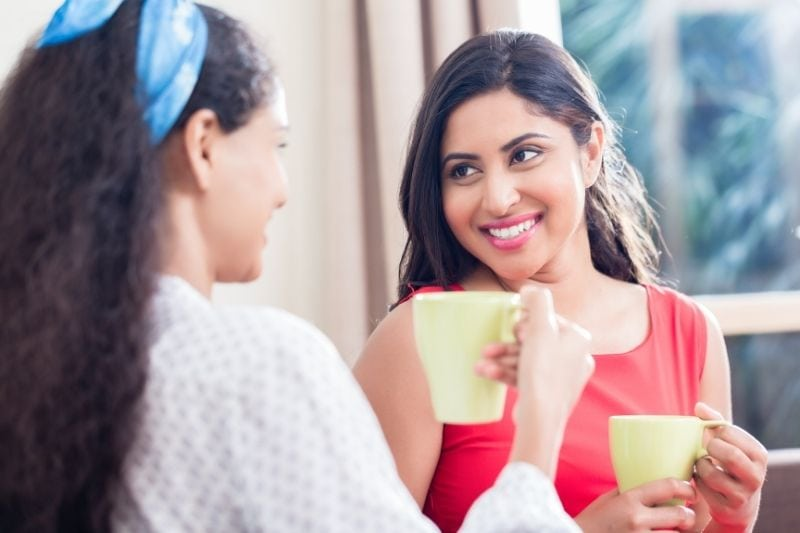 best friends drinking coffee together while chatting inside home