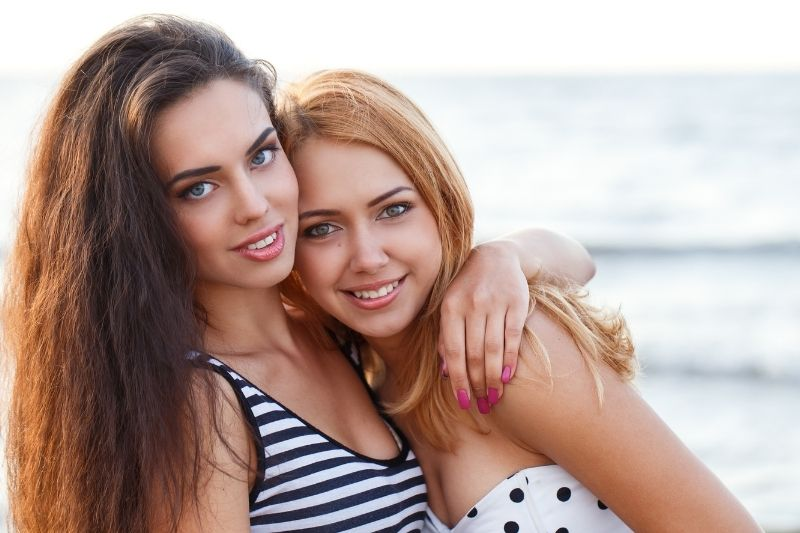 best friends hugging in the beach looking at the camera