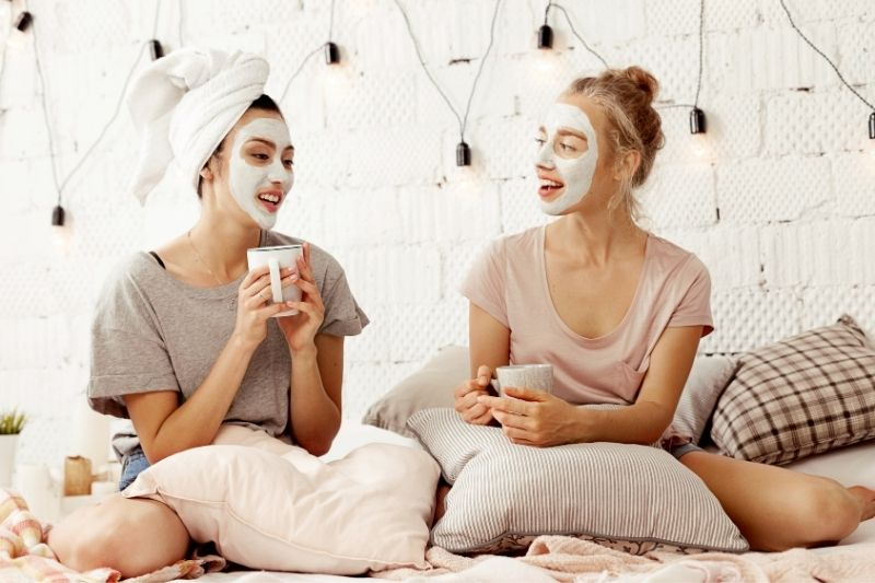 best friends talking with coffee insiding bedroom with face masks on their faces