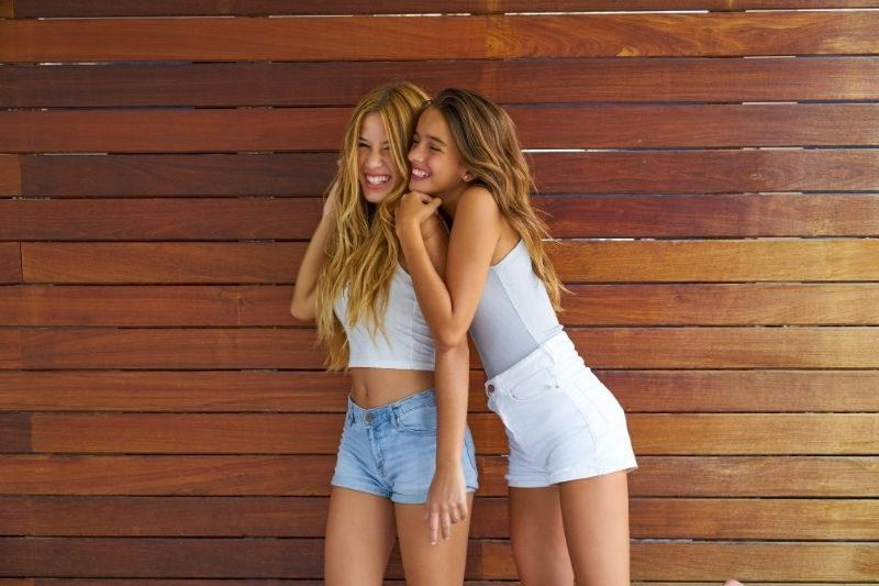 best friends teen girls hugging and standing againsts a wooden plank wall