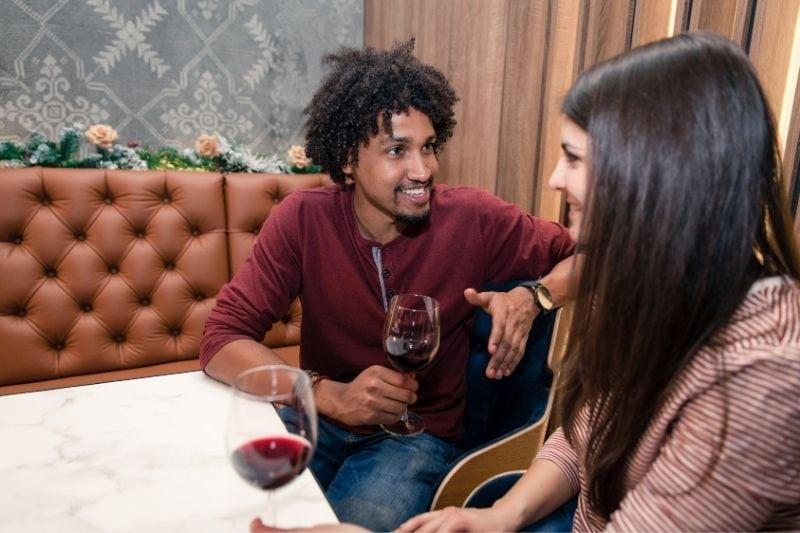 biracial couple in twenties having a date drinking red wine