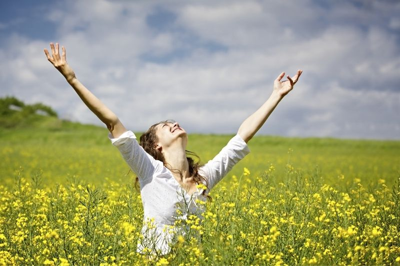blissful young woman raising her hands standing in the middle of the yellow flower field