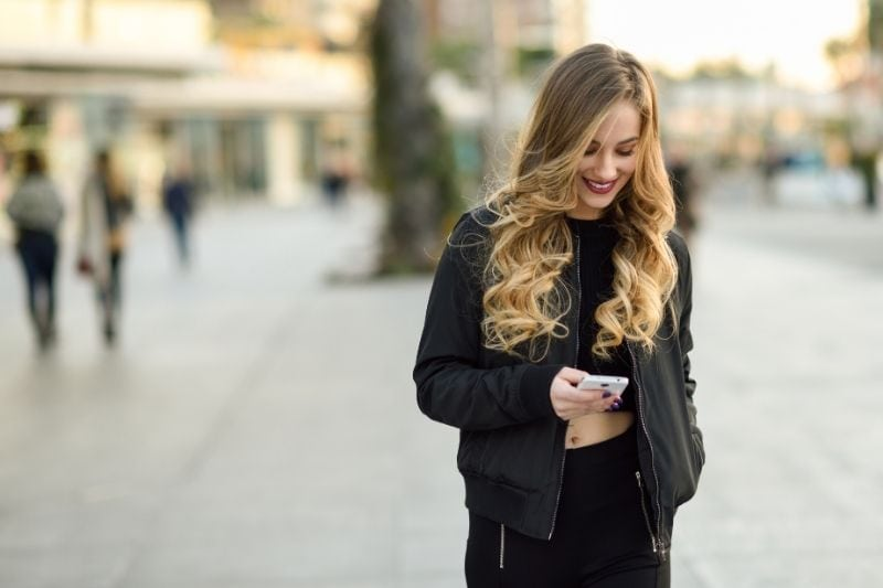 blonde woman texting in the middle of the street of the city