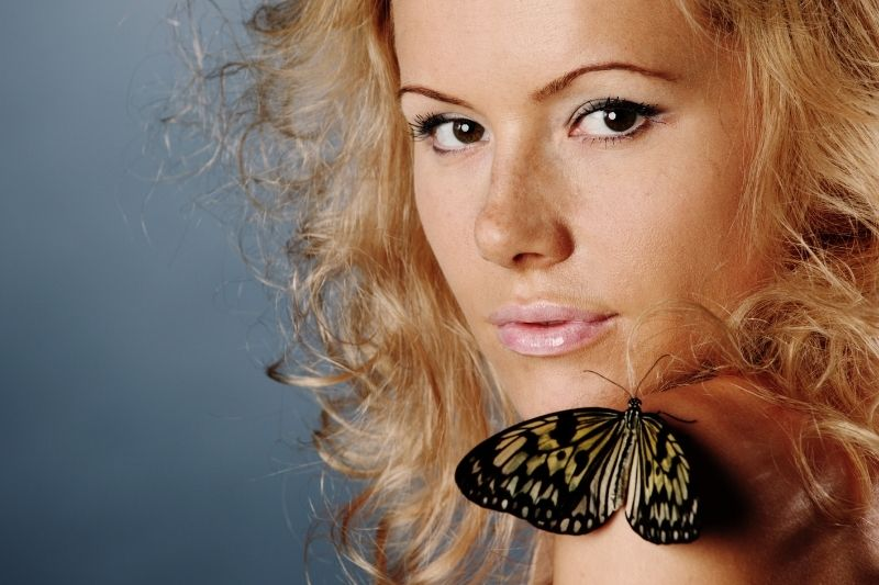 blonde woman with butterfly resting on her shoulder