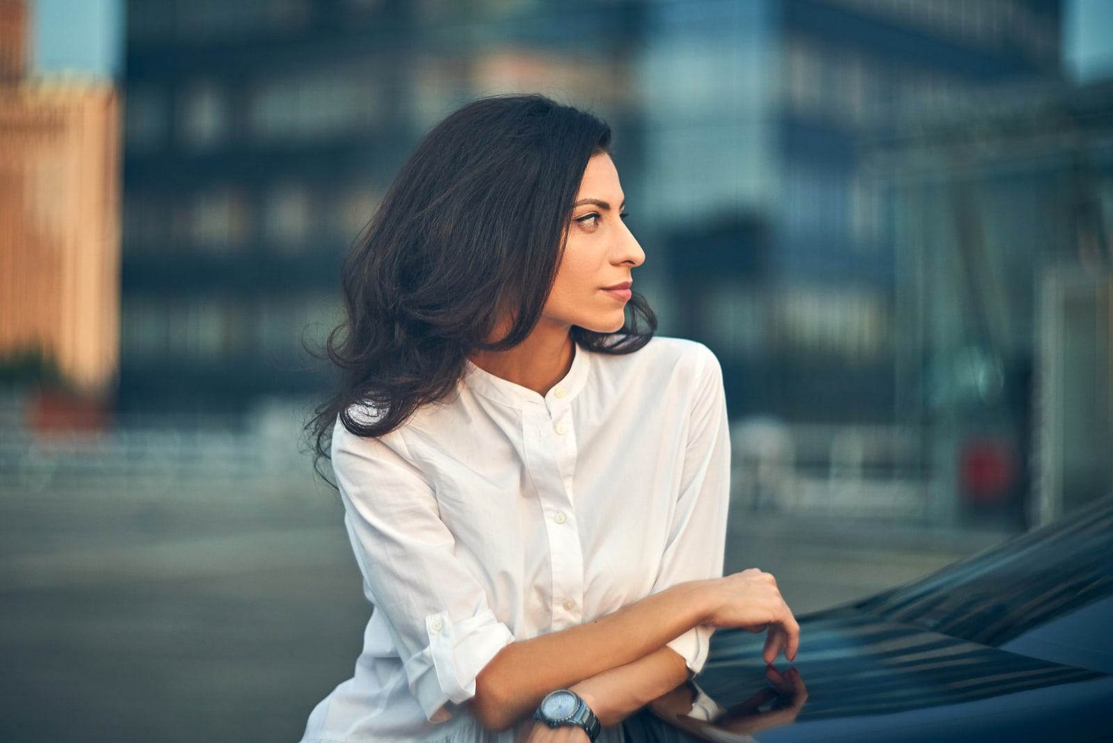 business woman standing outdoors leaning on the car