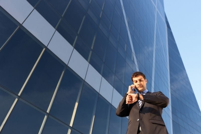 busy businessman on the phone checking his timepiece walking near a tall building phone on low angle
