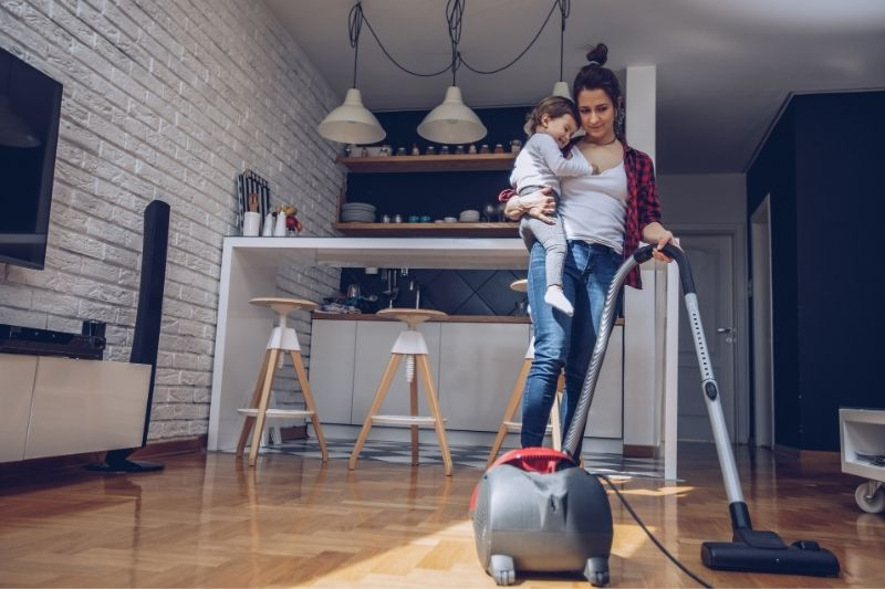 busy mother cleaning using a vacuum cleaner inside the house carrying a toddler