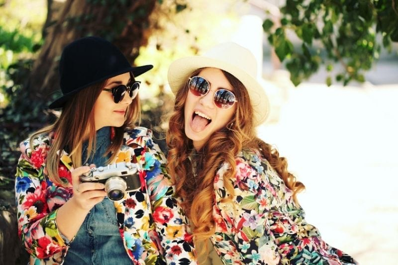 candid girls posing with twinning colorful jackets and hats carrying a camera