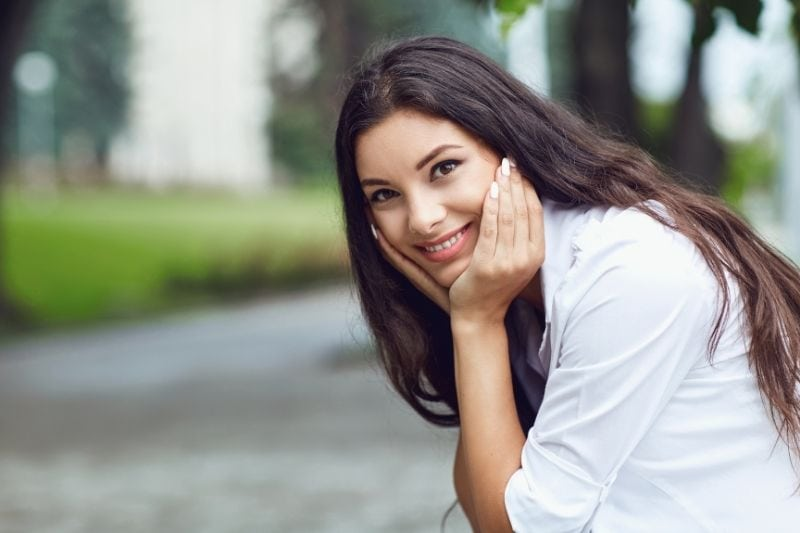 charming woman smiling with hands supporting her head while she sits along the street
