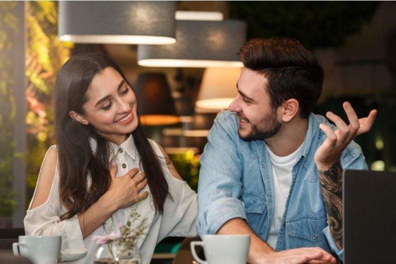 cheerful couple talking in a coffee date inside a cafe