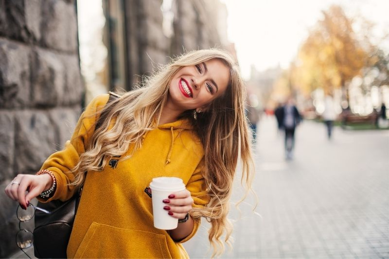 cheerful woman walking down the street holding a cup of coffee wearing yellow sweater